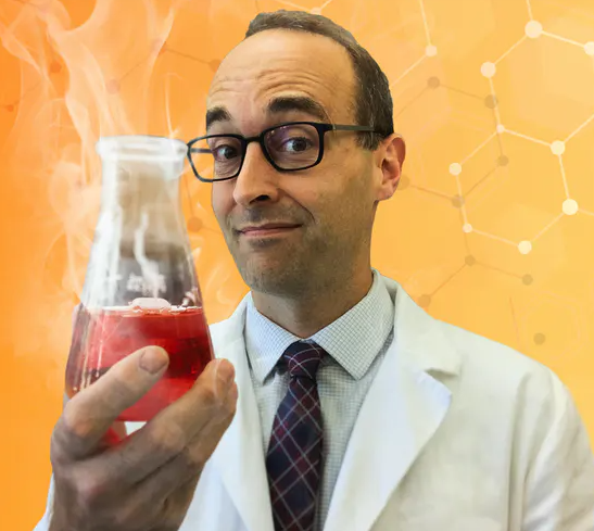 Scientist in glasses and lab coat holding a beaker